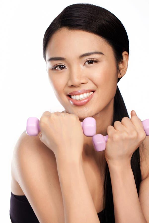 Donna asiatica attraente che risolve con i pesi fotografie stock libere da diritti