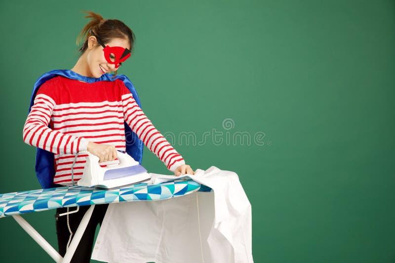 Donna asiatica attraente che riveste di ferro una camicia bianca su un backgrou verde fotografie stock libere da diritti