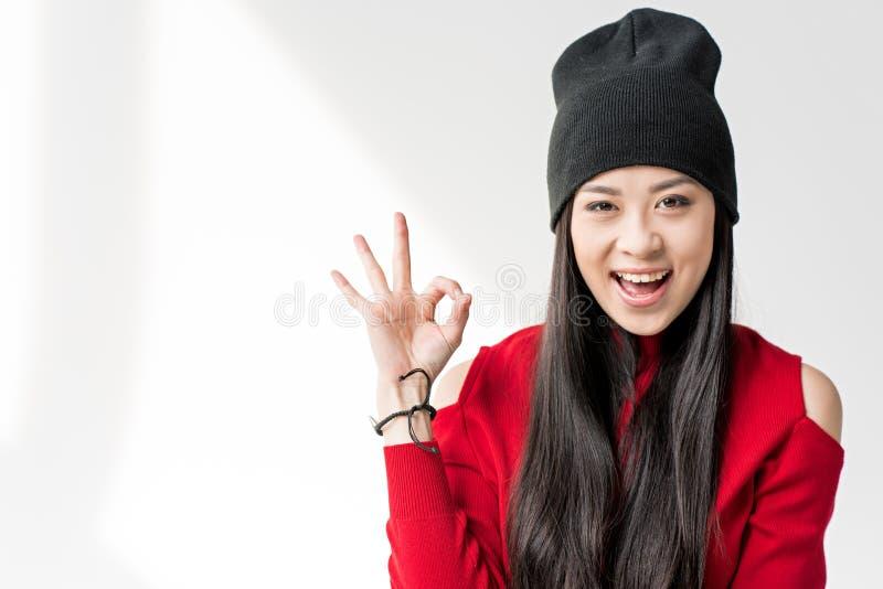 Donna asiatica attraente che si siede e che mostra segno giusto fotografia stock