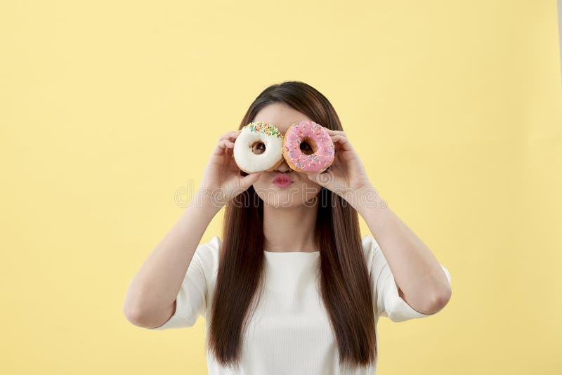 Donna asiatica attraente che tiene due guarnizioni di gomma piuma con l'espressione sorridente sveglia sopra fondo giallo fotografia stock libera da diritti