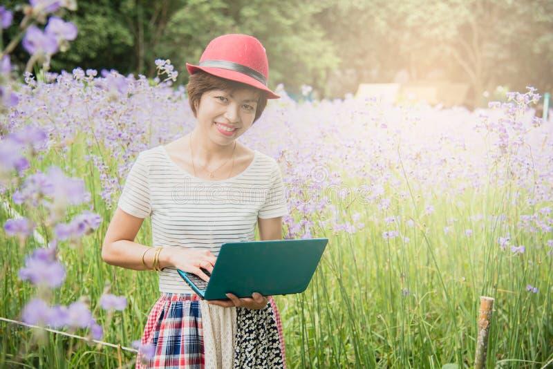 Donna asiatica attraente che utilizza computer portatile nel parco fotografie stock libere da diritti
