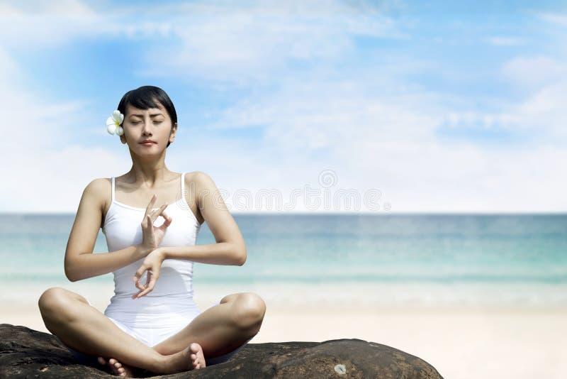 Donna asiatica bella che Meditating alla spiaggia fotografia stock libera da diritti