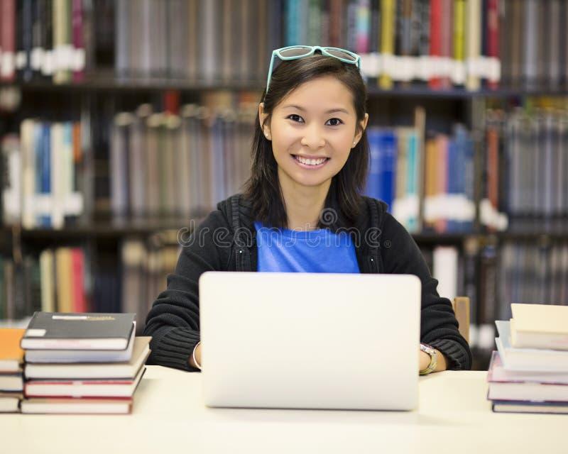 Donna asiatica in biblioteca con il computer portatile fotografia stock libera da diritti