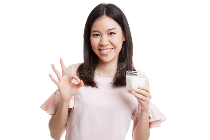 Donna asiatica in buona salute che beve un segno di APPROVAZIONE di manifestazione del bicchiere di latte fotografie stock