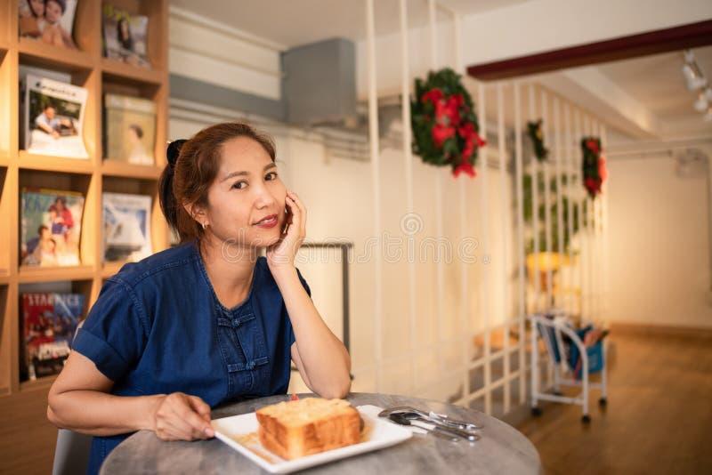 Donna asiatica in caffetteria che si siede alla Tabella che mangia Honey Toast fotografia stock libera da diritti