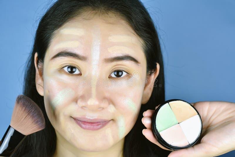 Donna asiatica che applica il fondamento di trucco dei cosmetici e che usando correttore di correzione di colore immagine stock