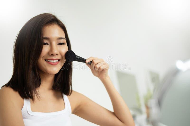 Donna asiatica che applica trucco con una spazzola fotografia stock libera da diritti