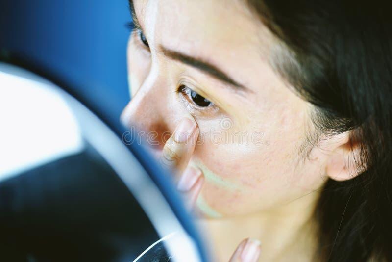 Donna asiatica che applica trucco dei cosmetici e che usando correttore di correzione di colore immagini stock