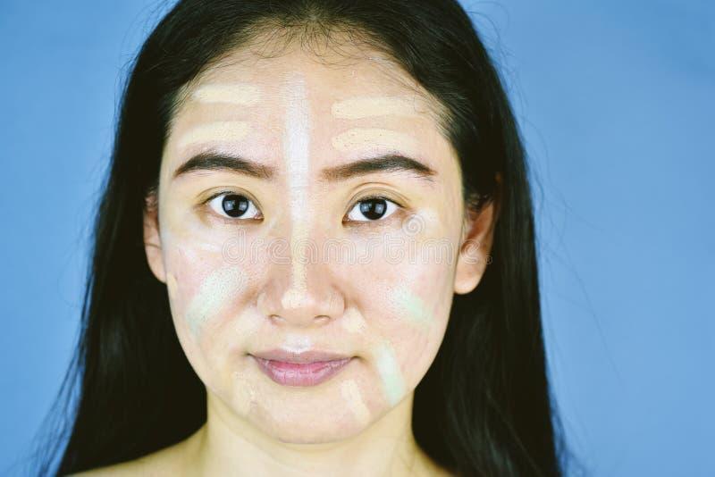 Donna asiatica che applica trucco dei cosmetici e che usando correttore di correzione di colore immagini stock libere da diritti