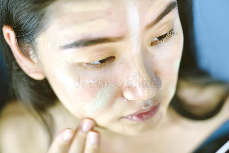 Donna asiatica che applica trucco dei cosmetici e che usando correttore di correzione di colore immagine stock libera da diritti