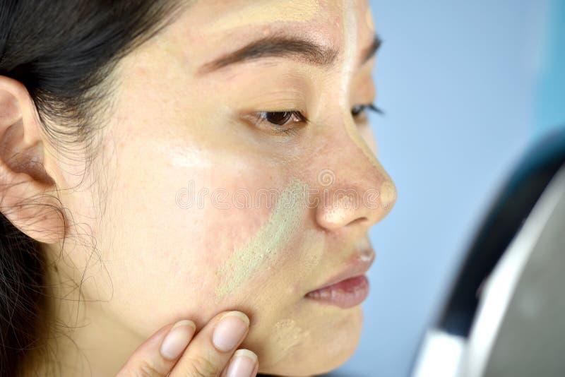 Donna asiatica che applica trucco dei cosmetici e che usando correttore di correzione di colore fotografia stock
