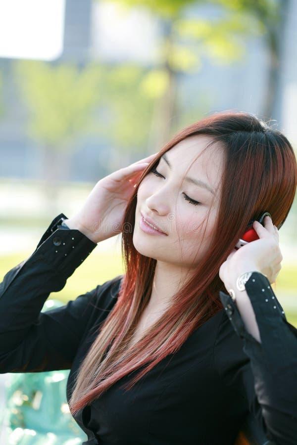 Donna asiatica che ascolta la musica fotografia stock