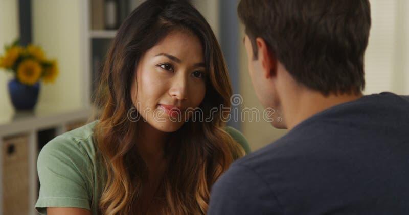 Donna asiatica che ascolta la sua conversazione del ragazzo fotografie stock