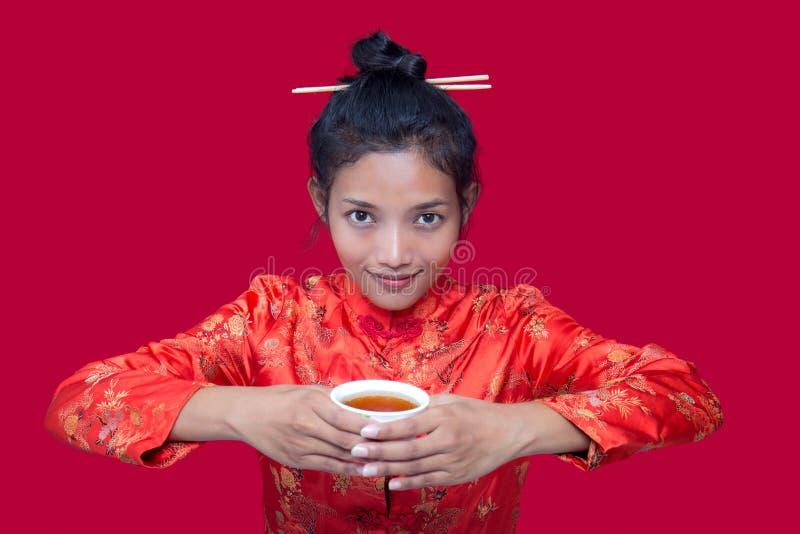 Donna asiatica che beve da una tazza fotografia stock libera da diritti