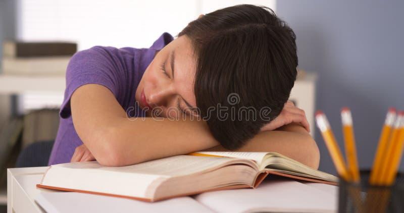 Donna asiatica che dorme sopra i libri fotografia stock