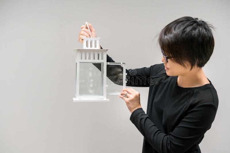 Donna asiatica che esamina la lanterna d'annata bianca vuota della candela fotografie stock libere da diritti