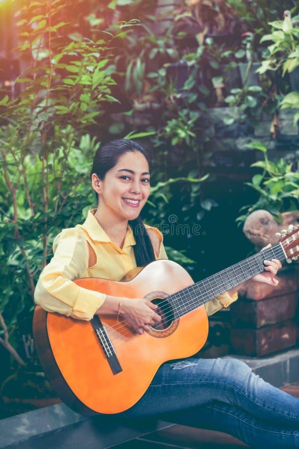 Donna asiatica che gioca chitarra acustica con luce solare luminosa Vinta immagini stock
