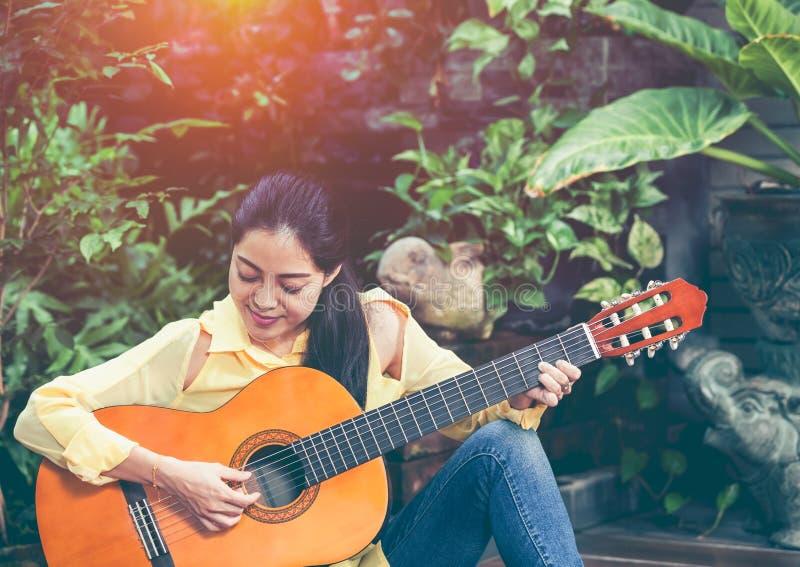 Donna asiatica che gioca chitarra acustica con luce solare luminosa Vinta immagine stock