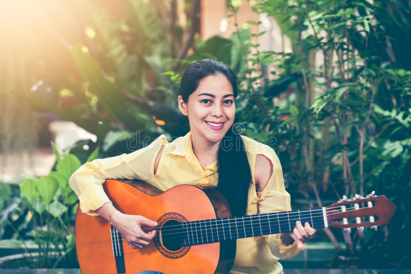Donna asiatica che gioca chitarra acustica con luce solare luminosa Vinta fotografia stock libera da diritti