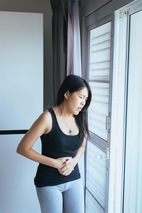 Donna asiatica che ha mal di stomaco doloroso, sofferenza femminile dal dolore addominale, crampi di periodo fotografia stock