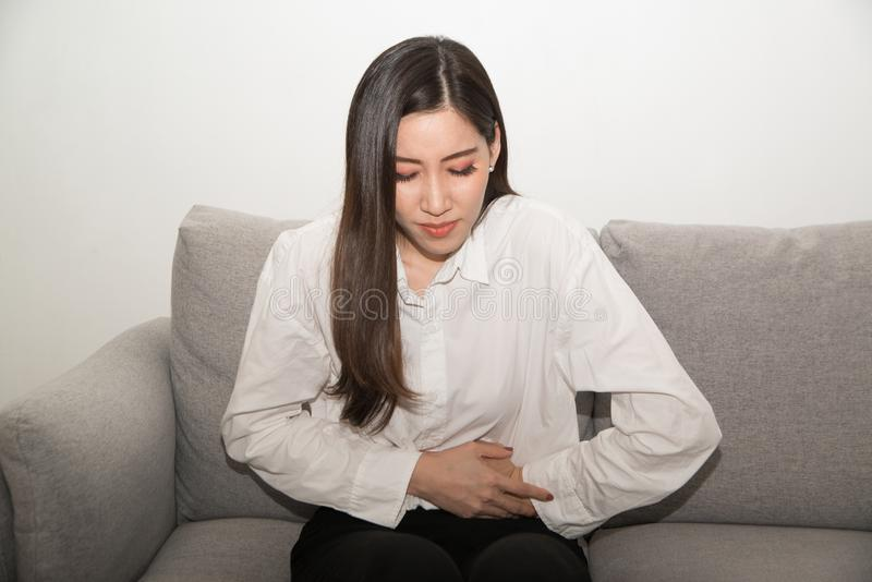 Donna asiatica che ha mal di stomaco doloroso, sofferenza femminile dal dolore addominale immagini stock