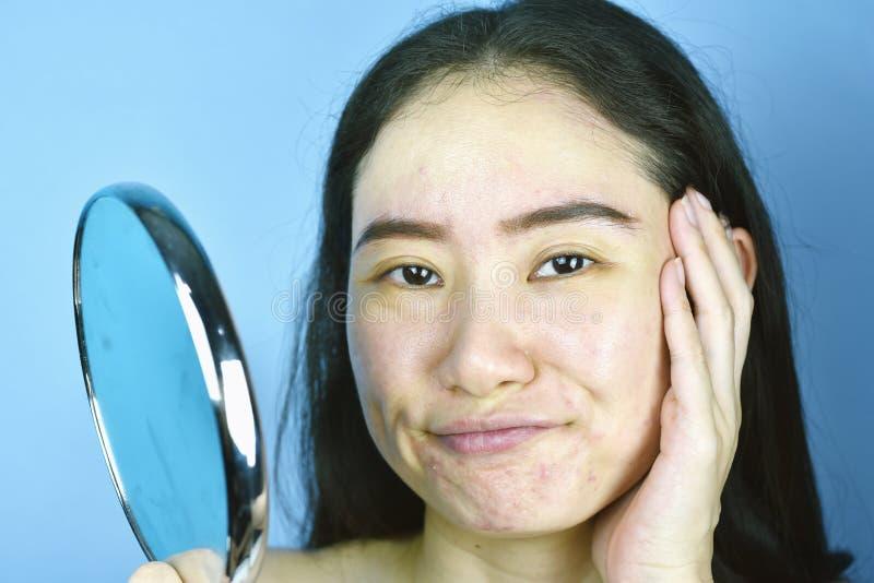 Donna asiatica che la esamina nello specchio, sensibilit? femminile per infastidire circa la sua manifestazione di aspetto di rif immagini stock