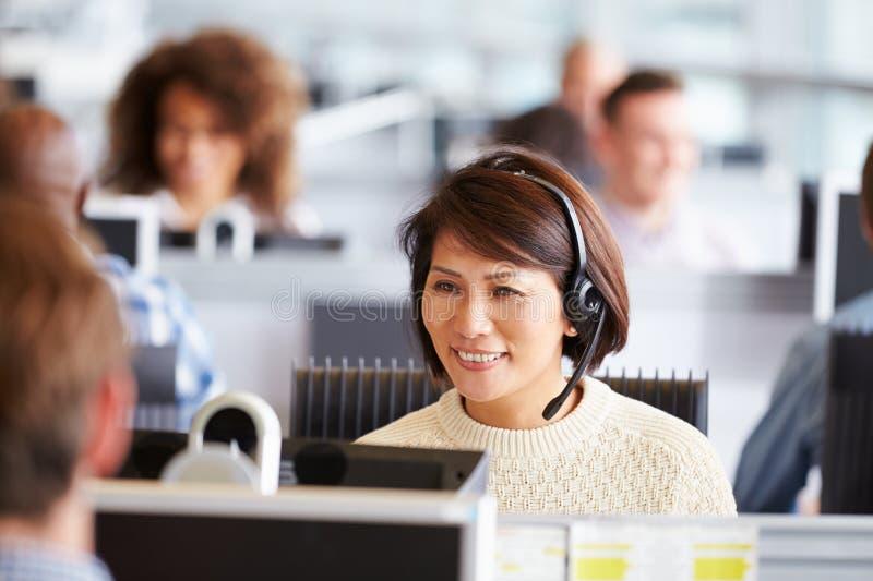 Donna asiatica che lavora nel call-center, circondato dai colleghi immagini stock libere da diritti