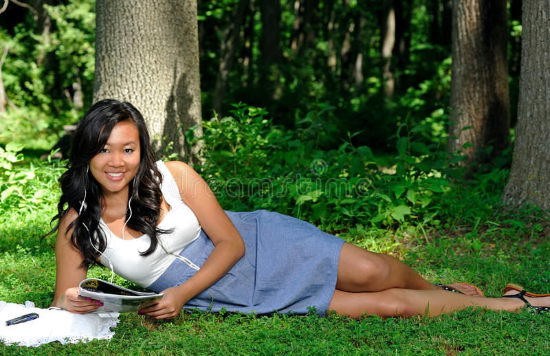 Donna asiatica che legge uno scomparto in sosta fotografia stock