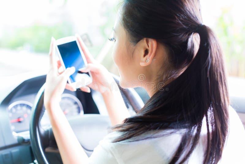 Donna asiatica che manda un sms mentre conducendo automobile immagini stock