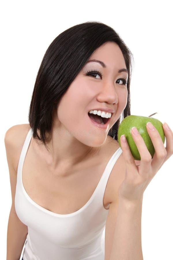 Donna asiatica che mangia Apple immagine stock