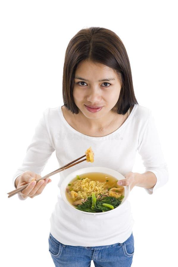 Donna asiatica che mangia con i bastoni di taglio immagine stock