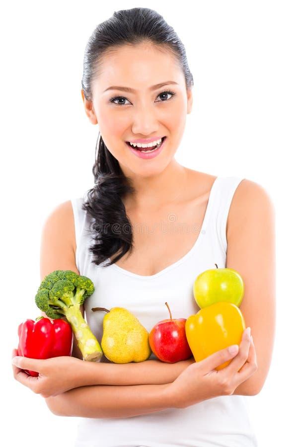 Donna asiatica che mangia frutta fotografie stock libere da diritti