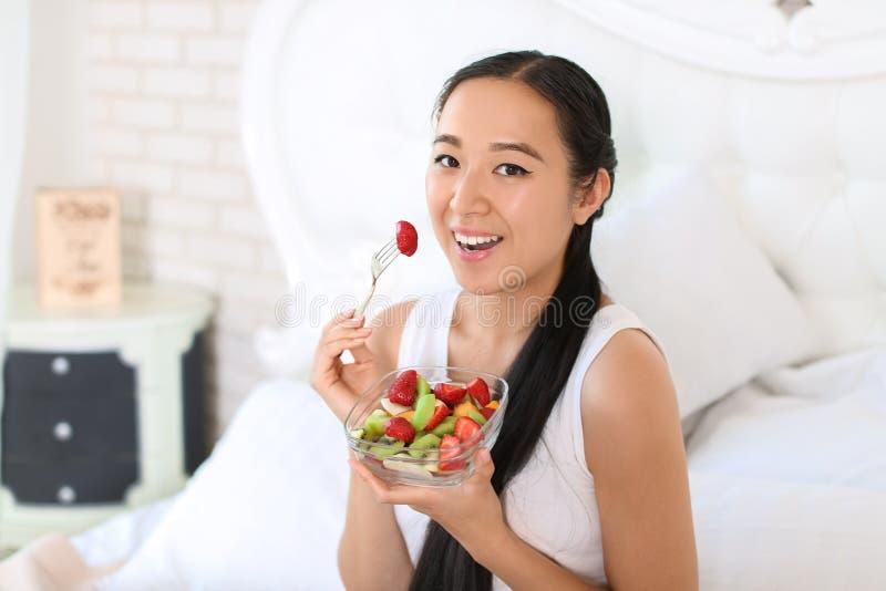 Donna asiatica che mangia macedonia sana a casa fotografie stock libere da diritti