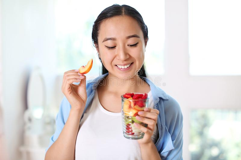 Donna asiatica che mangia macedonia sana a casa fotografia stock