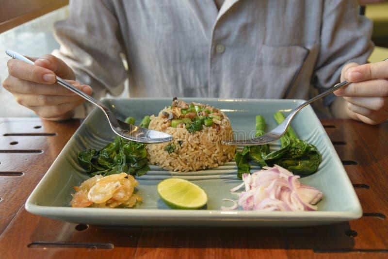 Donna asiatica che mangia riso fritto con il pesce ed il piatto laterale salati di immagini stock libere da diritti