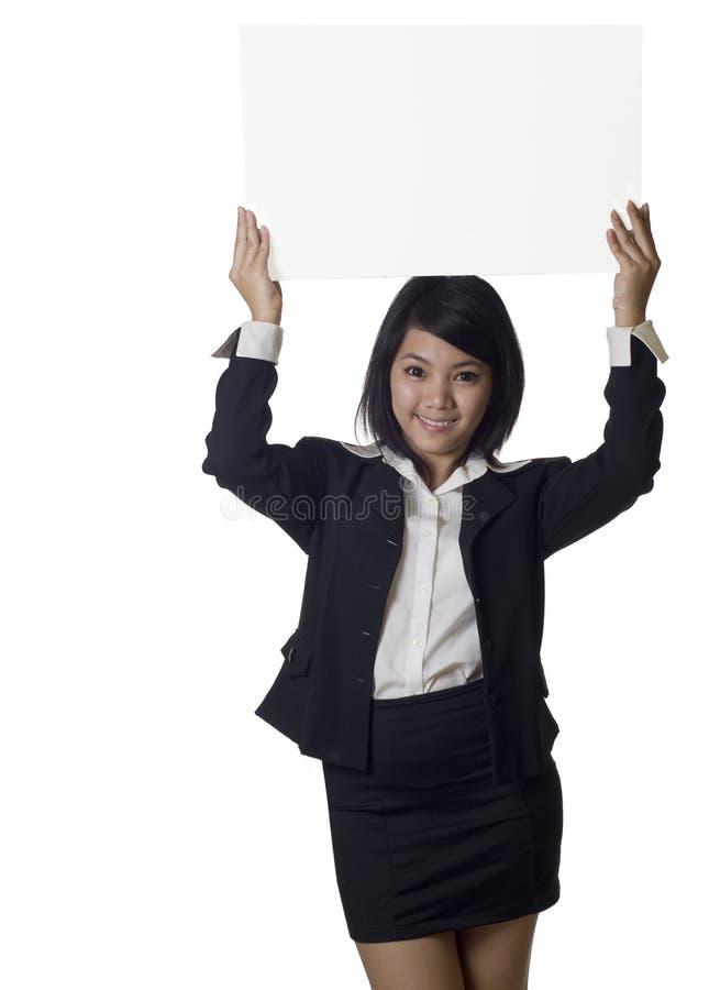 Donna asiatica che mostra la bandiera in bianco del segno del tabellone per le affissioni immagini stock libere da diritti