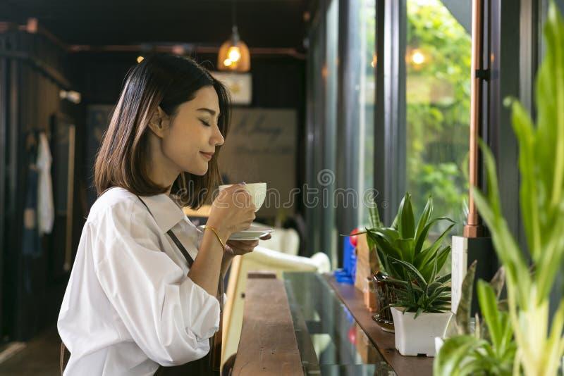 Donna asiatica che odora e che beve caffè caldo con sentiresi bene i fotografia stock libera da diritti