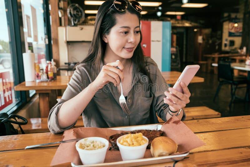 Donna asiatica che per mezzo del cellulare e caricare la foto fotografia stock
