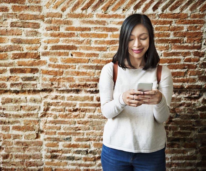 Donna asiatica che per mezzo del telefono cellulare immagine stock