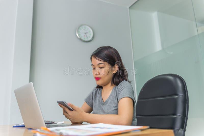 Donna asiatica che per mezzo dello smartphone per cercare informazioni su Internet fotografia stock libera da diritti