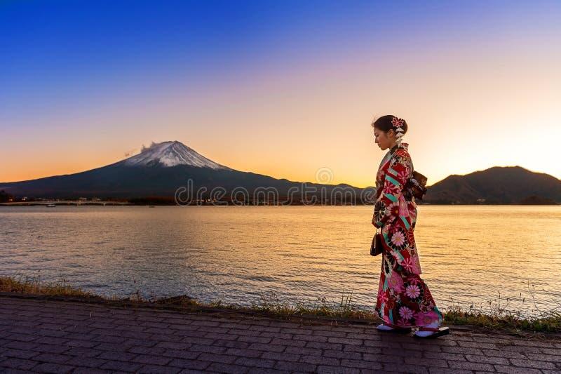 Donna asiatica che porta kimono tradizionale giapponese alla montagna di Fuji Tramonto nel lago Kawaguchiko nel Giappone immagini stock libere da diritti
