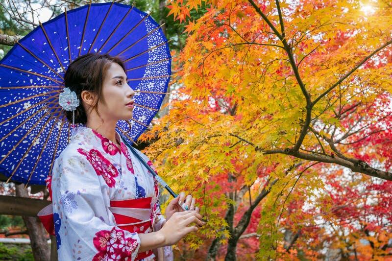 Donna asiatica che porta kimono tradizionale giapponese con l'ombrello nel parco di autunno japan fotografia stock