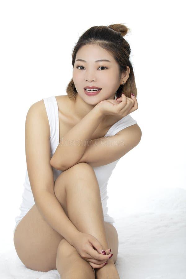 Donna asiatica che porta una camicia bianca su backround bianco immagini stock