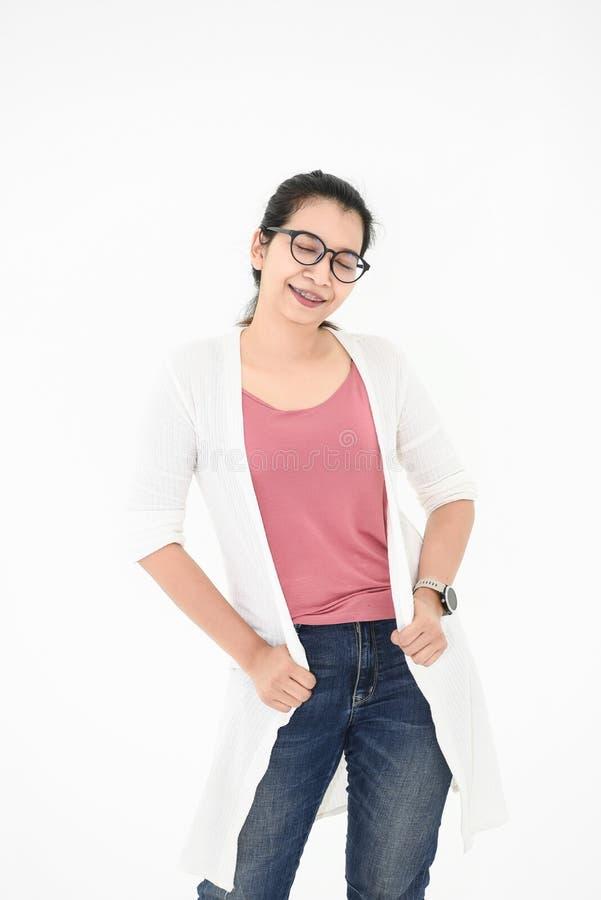 Donna asiatica che posa con l'attrezzatura e gli occhiali casuali nell'umore felice su fondo isolato bianco Gli occhi chiusi adat fotografia stock