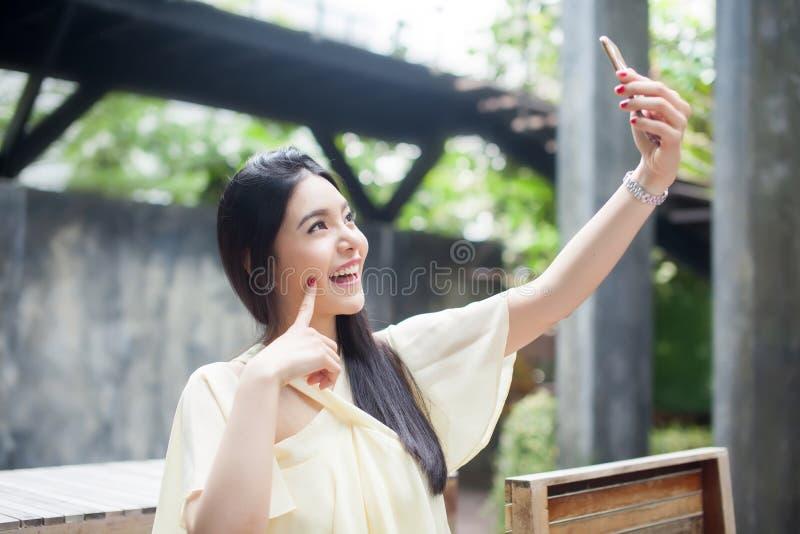 Donna asiatica che prende un selfie con il suo telefono in parco pubblico immagini stock