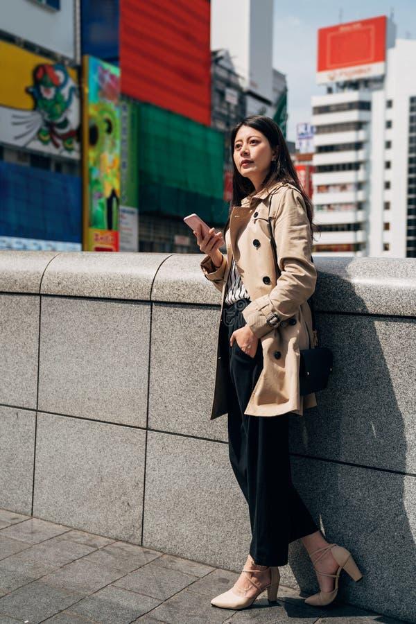 Donna asiatica che risponde i email sul telefono cellulare immagine stock libera da diritti