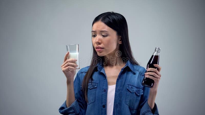 Donna asiatica che sceglie fra la bevanda gassosa non sana ed il latte sano utile fotografia stock libera da diritti