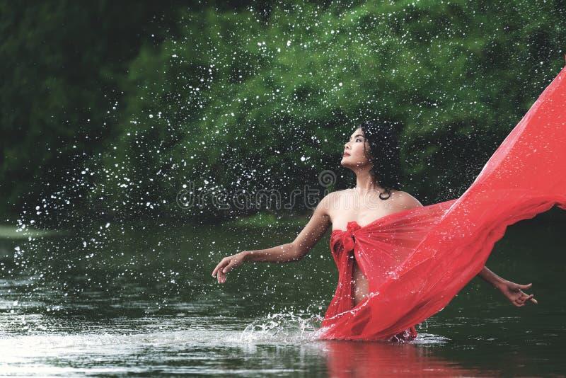 Donna asiatica che si rilassa e che gode del gioco con acqua e la spruzzata al fiume esotico tropicale con acqua stupefacente di  fotografia stock