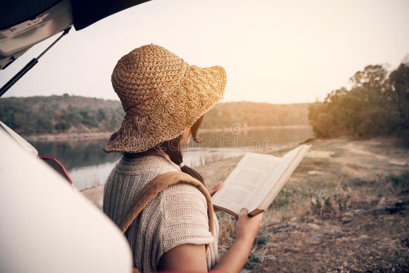 Donna asiatica che si siede in automobile di eco e che legge un libro fotografie stock libere da diritti