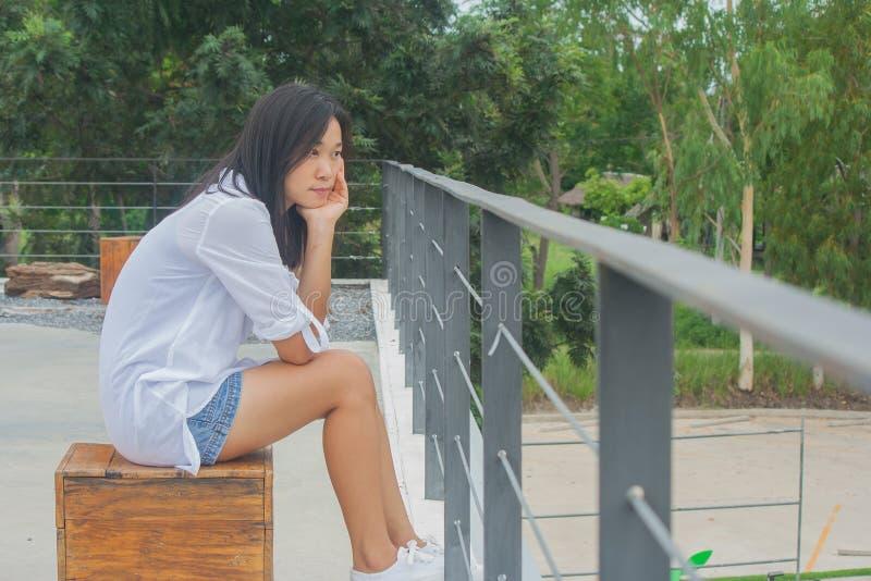 Donna asiatica che si siede sulla sedia di legno alla cima piana delle costruzioni del tetto, rilassantesi e guardante in avanti immagini stock